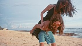 Attractive young and energetic couple having fun on the beach. Woman piggyback riding a man and laughing. Sea Summer. Attractive young and energetic couple stock video footage