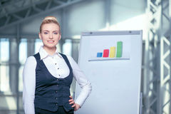 Attractive young engineer is creating sketches of. Professional businesswoman is working on plan of building. She is standing near a whiteboard with diagram and Stock Images