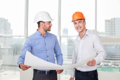 Attractive young engineer is explaining the plan. Handsome architect is showing sketching of construction to a builder. The foreman likes his idea. He is smiling Stock Images