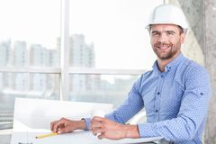 Attractive young engineer is projecting a new. Handsome architect is sitting at the table and drawing sketches of construction. He is drinking coffee and smiling Royalty Free Stock Photography
