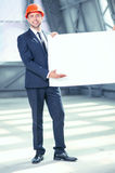 Attractive young engineer is showing the new. Handsome architect is presenting the plan of building. He is standing and holding a large empty blueprint. The man Royalty Free Stock Image