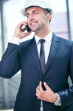 Attractive young engineer is talking on the phone. Cheerful architect is communication with his customer by telephone. He is standing and smiling. The man is Royalty Free Stock Photography
