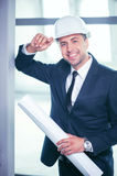 Attractive young engineer is working on new. Handsome architect is standing and holding a blueprint in his hand. He is touching a white helmet and smiling. The Royalty Free Stock Photo
