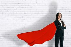 Confidence and power concept. Attractive young european businesswoman with red cape and shadow standing on brick wall background. Confidence and power concept stock photo