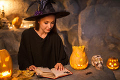 Attractive young evil witch is conjuring with Stock Photos