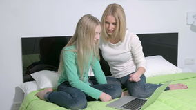 Attractive young family or mother and daughter using a laptop to make future plans.  stock footage