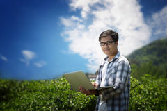 Attractive young farmers with a laptop sitting in a garden . Royalty Free Stock Photo