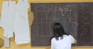 Attractive young fashion designer woman working at studio. Woman at work as fashion designer and tailor, looking at sketches in atelier stock video footage