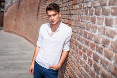 Attractive young fashion man leaning on a brick wall Stock Images