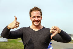 Attractive young fashion man showing the thumbs up and down gest Stock Photos
