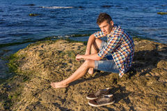 Attractive young fashion sexy man on rock near the sea water. Attractive young fashion sexy man sitting on a rock near the sea water with shoes beside him Stock Images