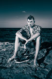 Attractive young fashion sexy man on rock near the sea water in. Attractive young fashion sexy man sitting on a rock near the sea water with shoes beside him in Stock Photos