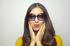 Attractive young fashion woman with sunglasses seduce the camera. Girl with beautiful hair looking at camera with hands on her fac. E. Gray background Stock Photos