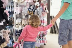 Attractive young father choosing baby clothes. Attractive young man and his cute little daughter at the kids apparel shop, bying clothes together Royalty Free Stock Photos