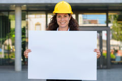 Attractive young female architect holding a sign. Attractive young female architect or structural engineer wearing a hardhat standing in front of a glass fronted Royalty Free Stock Photos