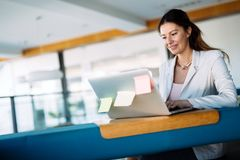 Attractive young female architect working on laptop. In office Stock Image