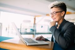 Attractive young female architect working on laptop. In office Stock Images