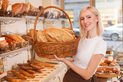 Attractive young female baker with fresh pastry Royalty Free Stock Images
