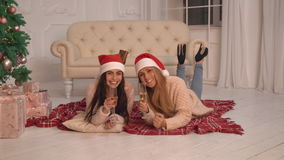 Attractive young female celebration new year indoor. Women drinking champagne near christmas tree at home. Happy lady celebrating new year flutes together in a stock footage