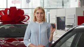 Cheerful beautiful young woman showing keys to her new car royalty free stock images