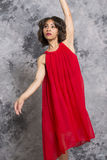 Attractive, young, female dancer standing in a red dress. Female dancer in red dress, standing against a grey background with an elegant gesture royalty free stock images