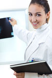 Attractive young female doctor examining x-ray results Stock Photo