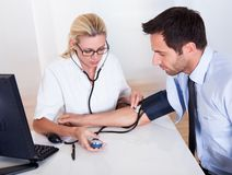 Doctor taking a patients blood pressure Stock Image