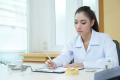 Attractive young female doctor sitting at desk in office Royalty Free Stock Photo