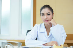 Attractive young female doctor sitting at desk in office Stock Photo
