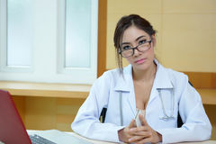 Attractive young female doctor sitting at desk in office Royalty Free Stock Images