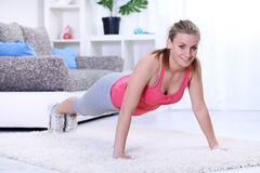 Attractive young female doing push ups. Attractive young lady doing push-ups on carpet at home stock images