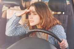 Attractive young female driver looks attentively at windscreen into distance tries to see something in foreground, understand what. Is going on road, sits at Royalty Free Stock Photo
