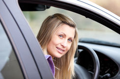 Attractive young female driver sitting in her car Royalty Free Stock Photos
