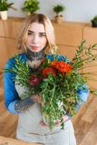 Attractive young female florist holding flower bouquet and looking. At camera stock image