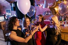 Attractive young female friends celebrating a holiday standing with glasses of wine in trendy bar royalty free stock image