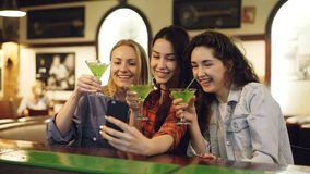Attractive young women are taking selfie with cocktails in bar. Cheerful girls are posing, laughing and clanging glasses stock video