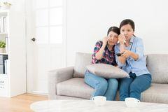 Attractive young female friends watching tv. Show and feeling sad crying sitting on sofa couch Royalty Free Stock Image