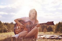 Attractive young female guitarist uses music instrument, plays guitar, sings song, produces wonderful sound or melody, sits crosse. D legs on plaid, poses royalty free stock photos