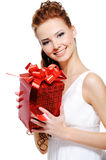 Attractive young female holding present over white Royalty Free Stock Images