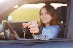 Attractive young female holds car keys, being happy owner of new automobile, blurred background. Lovely woman sells vehicle, adver. Tises it, shows keys at Stock Image