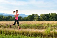 Attractive young female jogging Royalty Free Stock Image