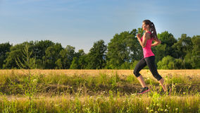 Attractive young female jogging in countryside Royalty Free Stock Image
