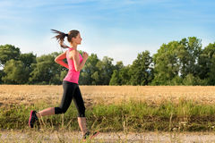 Attractive young female jogging in countryside Stock Photography
