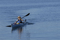 Attractive young female kayake. R is rowing in deep blue sub-tropical waters of Mission Bay, San Diego, California Royalty Free Stock Image
