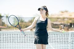 Tennis player taking break after practicing. Attractive young female player in her 20s standing by a tennis net on court and looking away at copy space Royalty Free Stock Photo