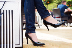 Attractive young female in black high heels enjoying a break after successful shopping royalty free stock photography