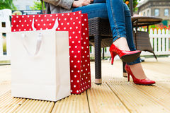 Attractive young female in sexy red high heels enjoying a break after succesfull shopping Stock Images