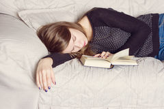 Attractive young female is sleeping on sofa  with book Royalty Free Stock Photo