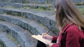 Attractive young female student preparing for lectures in University while sitting on the stairs, writing notes in her Stock Image