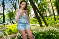 Attractive young female surfing the Internet with her smartphone Stock Photos